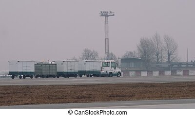 A luggage tractor with passenger baggage in fog