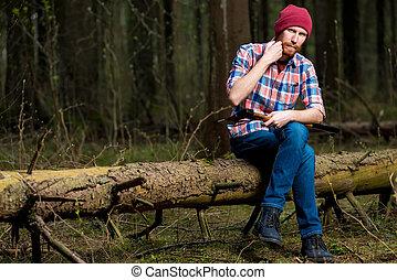 a lumberjack in the woods resting on a fallen tree