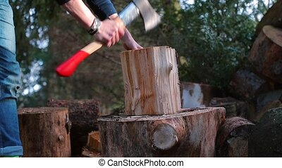A lumberjack makes light hits on a wooden block with an ax.