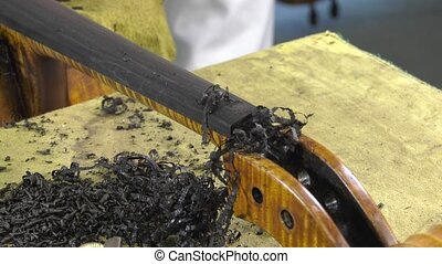 luthier shapes ebony fingerboard with a wood planer