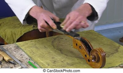 a luthier repairs a cello