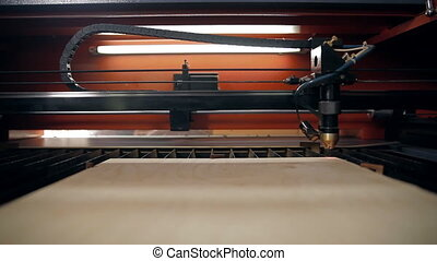 A machine for cutting plywood with a laser - The machine is...