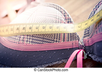 Macro Of A Bra With Measuring Tape On Top On A Table - Measure Breast Size Concept