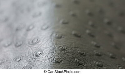 A macro shot of dark gray perforated artificial leather...