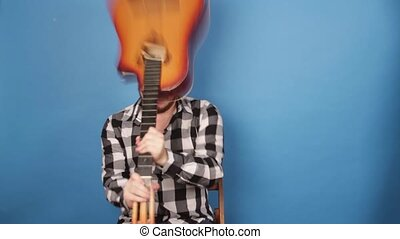 A mad man hits himself on the head with a guitar. The guy ...