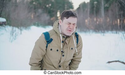 A mad man squirts a pepper spray to his face in the winter forest.