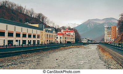 A main street of the small mountain town in spring with a river that divides the town into two parts. Sochi, Roza Khutor, Russia.