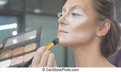 A make-up artist does the make-up of the model. Apply a special brush with a tonal paint. Preparation for an artistic photo shoot