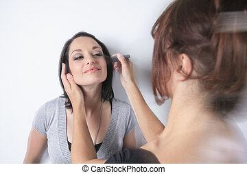 A makeup pro woman working on a fashion model