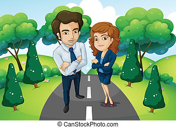 A male and a female standing in the middle of the road