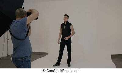 A male artist, he participates in a photo shoot. Against the...
