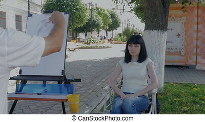 A male artist is writing, drawing a portrait of a young...