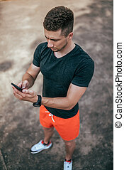 A male athlete holds a phone in his hand, launches an application for a workout, in summer on nature view from the top on the background of asphalt. Internet application, social networks online.