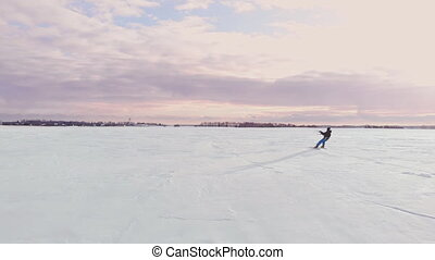 A male athlete in sports outfit is doing snow kiting on beautiful winter landscape