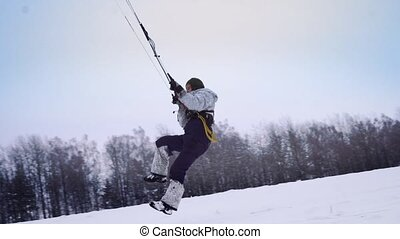 A male athlete in sports outfit is doing snow kiting on...