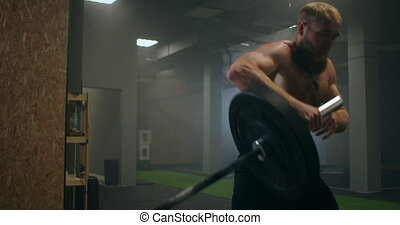 A male athlete lifts a weight bar with one hand in slow motion. Strength training for a boxer. The man is sweating working out in the gym practicing the force of the blow with his hand