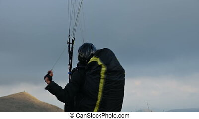A male athlete paraglider raises a wing in an outdor against...