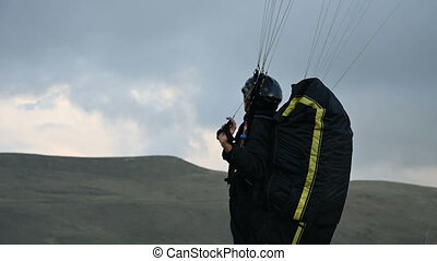A male athlete paraglider raises a wing in an outdor against the backdrop of evening clouds but cannot fly. Failure while trying to take off.