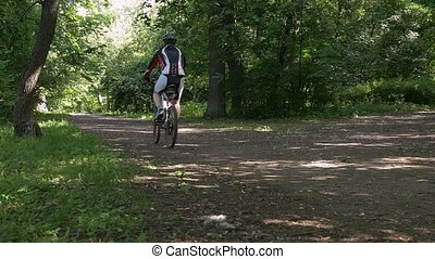A male athlete riding a bicycle in the park. slow motion
