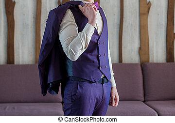 male businessman putting on blue suit