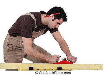 A male carpenter using a plane.