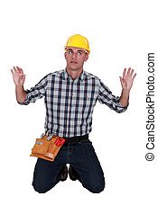 A male construction  worker trapped in an invisible box.