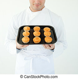 A male cook holding muffins