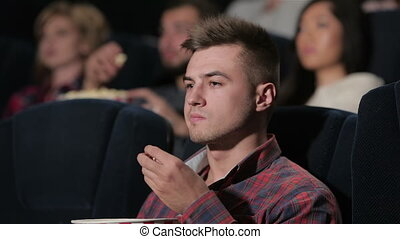 A male disappointed in a movie theater - Young man in a ...