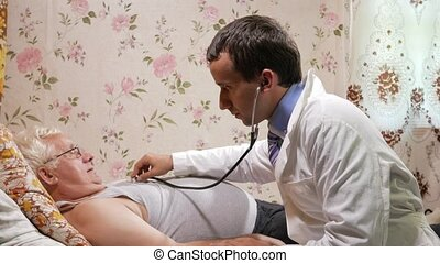 A male doctor listens to a patient with a phonendoscope at home. The man is lying on the couch.