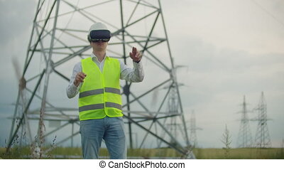 A male electrician in virtual reality glasses moves his hand...
