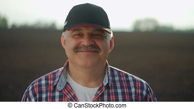A male farmer in a baseball cap and looking at the camera smiling after a working day.
