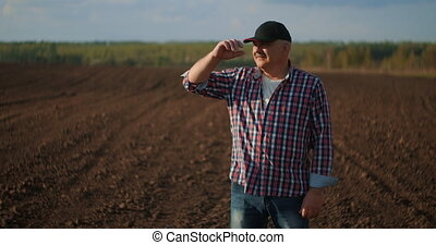 A male farmer takes off his baseball cap and looks at the sunset after a working day. a farmer looks at the sunset in a plowed field