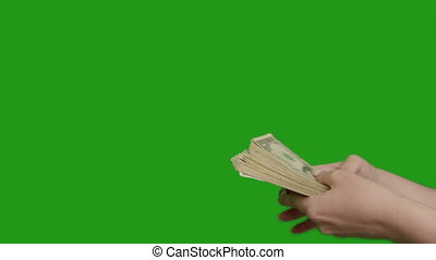 Male hand holds out a large bundle of money to a female hand, transaction, handshake, green screen