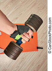 a male hand is on a glove with a dumbbell against a background of a quarantine fitness mat at home on a light wooden floor