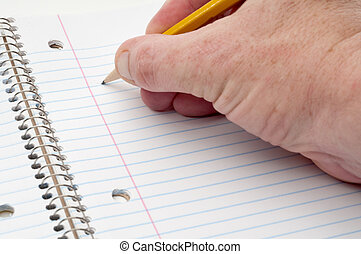A male hand ready to write with a pencil on lined notepaper
