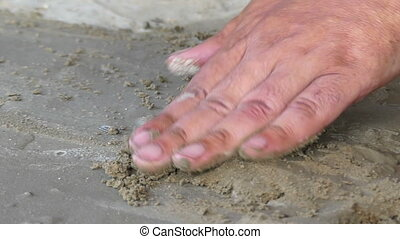 A male hand uses spatula on a lake bank covered with sand -...