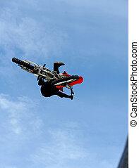 A male motox rider flies through the air doing a trick.