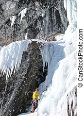 male mountain guide climbing a steep frozen waterfall on a cold winter day in the Alps