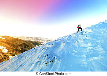 A male mountaineer walking uphill on a glacier. Mountaineer reaches the top of a snowy mountain in a sunny winter day.