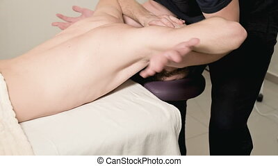 A male physiotherapist does a power stretching for a male...
