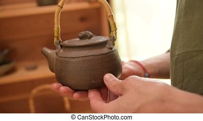 A male potter shows his work Yixing clay teapot for a handmade tea ceremony nearby. Shallow depth of field.