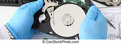 male repairman wearing blue gloves is holding a hard drive -...