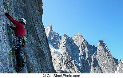 male rock climber on a steep granite route in the mountains near Chamonix in the French Alps