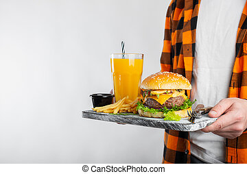 A male student in a checkered orange shirt on a white background is holding a wooden Board with a fresh Burger, a glass of orange juice and fried potatoes. With copy space for text