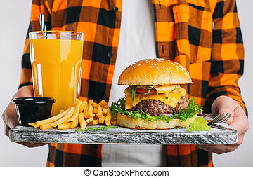 A male student in a checkered orange shirt on a white background is holding a wooden Board with a fresh Burger, a glass of orange juice and fried potatoes. The concept of unhealthy eating