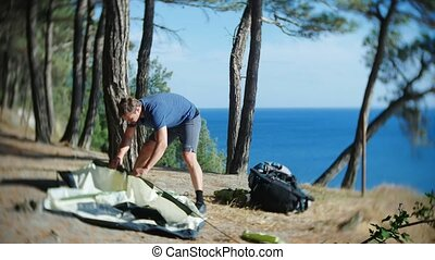 a male tourist arranges a tent on the edge of a steep...