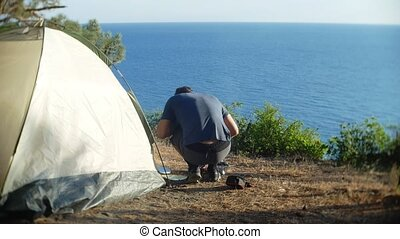 a male tourist prepares a meal next to a tent on the edge of a steep shore bank in a pine grove with a magnificent view of the sea landscape. 4k.