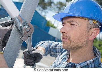 a male worker erecting scaffolding