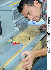 a male worker measuring workspace