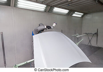 A male worker paints with a spray gun a part of the car body in silver after being damaged at an accident. Hood from the vehicle during the repair in the workshop auto service.